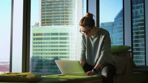 Business woman in glasses is sitting on a soft couch by panoramic window and opening the laptop to start working