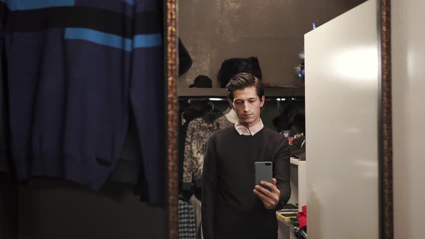 Young man is posing in front of mirror in a brand new clothes. He is taking pictures on his smartphone indoor. | Shutterstock HD Video #1009976264