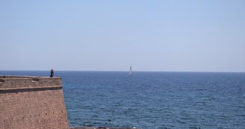 ALGHERO, SARDINIA, ITALY – JULY 2016 : Video shot of a beautiful girl enjoying view from city wall of Alghero on a sunny day with boat and sea in view