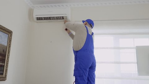Professional mature master installs the air conditioning in the room