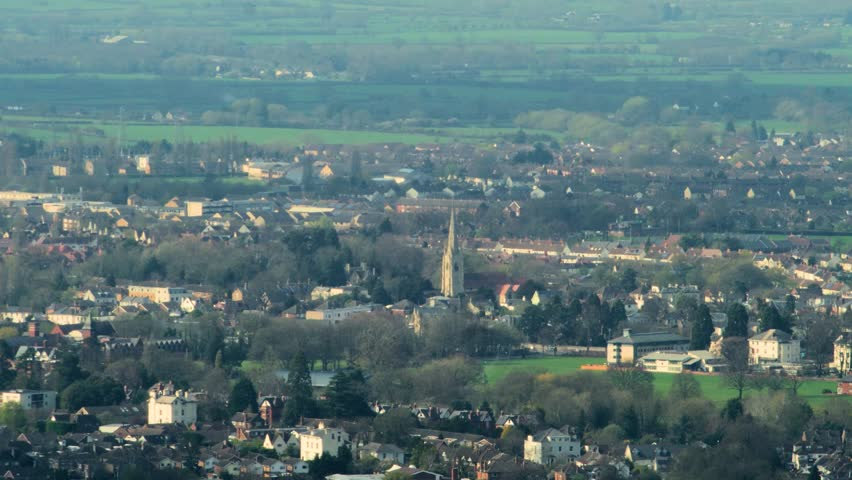 Distant town, Cheltenham, UK, with church steeple, shot with long vintage telephoto lens.