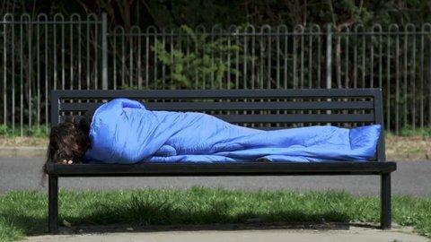 A homeless man sleeps in a sleeping bag on a park bench