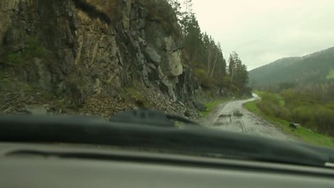 Inside of a car, driver place point of view, driving country road at rainy weather day, water drops. Rain drops on a windshield. A view of the road in Altai from the car.