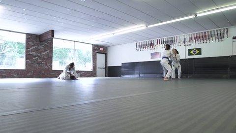 Four people practicing Jiu-jitsu
