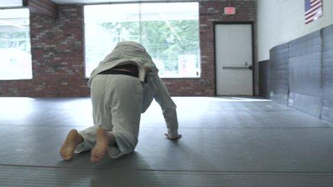Instructor practicing Jiu-jitsu moves with a boy