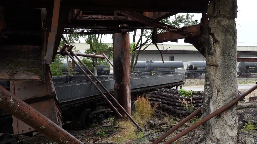Train traveling past old industrial yard