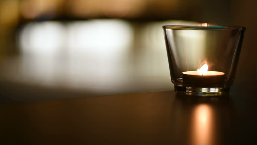 Romantic candle burns on the background of blurred. Fire in a candle holder in the dark.
