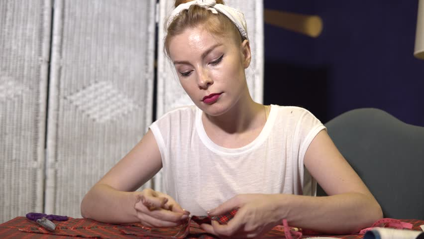 Young tailor sewing with a needle and thread by hand with chequered fabric. | Shutterstock HD Video #1010066084