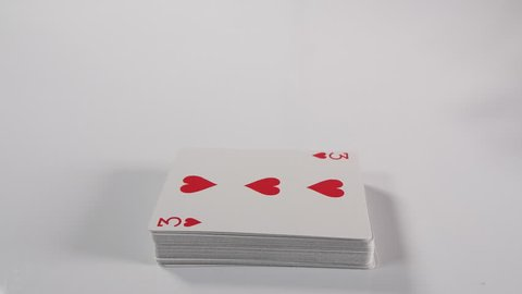 slow motion of a Mans hand spreading a playing card deck on a white surface background. Magician or casino dealer playing with cards. Dolly tracking shot of hand.