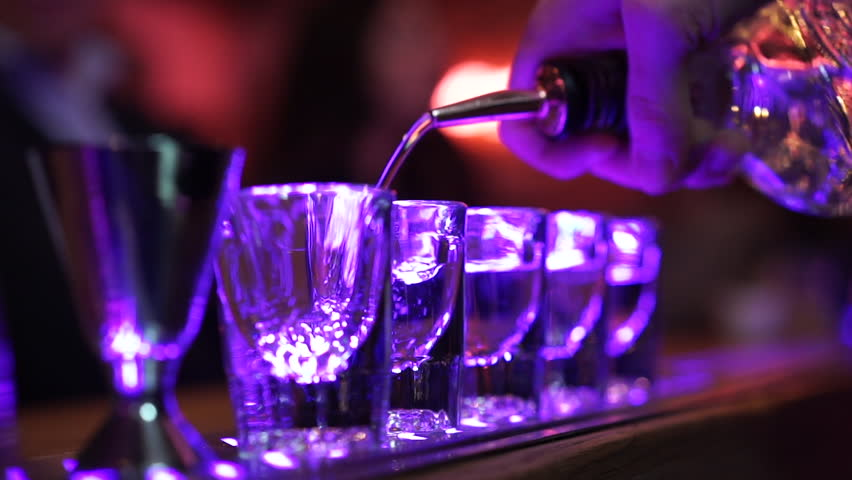 Shots of alcohol being poured on bar