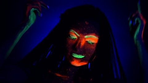Fashion model woman with braids dancing in neon light. Fluorescent makeup glowing under UV black light. Night club, party, halloween psychedelic concepts.