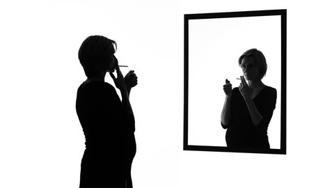 Conscience-stricken pregnant woman smoking cigarette in front of mirror, habits