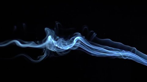 Blue smoke billow and swirl in slow motion on black background