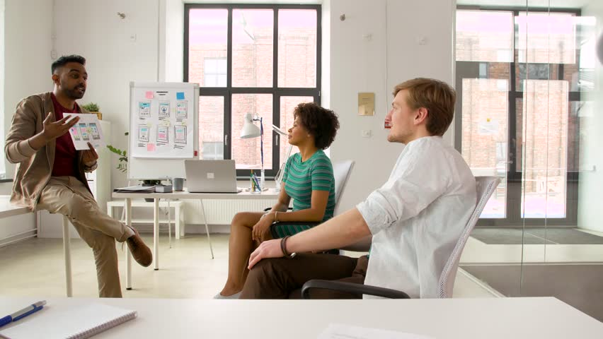 Business, technology and software development concept - man showing user interface mockup to creative team at office | Shutterstock HD Video #1010147204