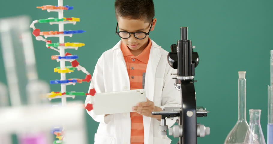 Schoolboy using digital tablet during experiment against turquoise background 4k | Shutterstock HD Video #1010152814