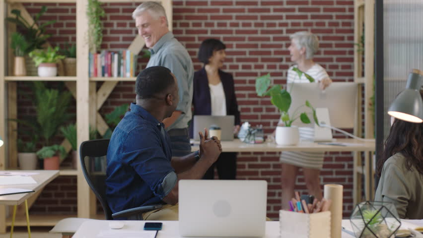 Happy african american businessman cheering excited celebrating success victory business team enjoying congratulating colleague in diverse office workspace | Shutterstock HD Video #1010156984