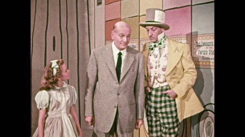 1950s: Girl walks down hallway with man and mad hatter. Woman with hat over head walks behind them, man talks, stops in front of large film reel. Mad hatter and hat covered woman operate projector.