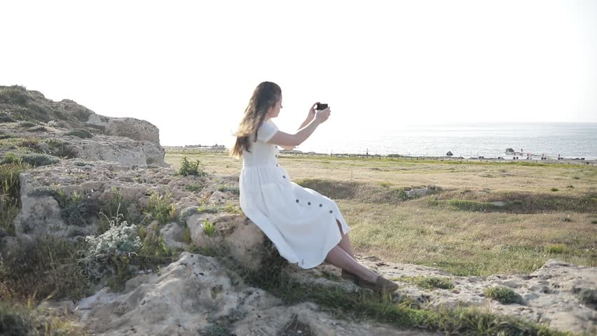Young girl does photo near to the blue sea sitting on a mountain Woman Watching Sunset. Takes Panorama Photos On Phone. Hair in the Wind | Shutterstock HD Video #1010172164