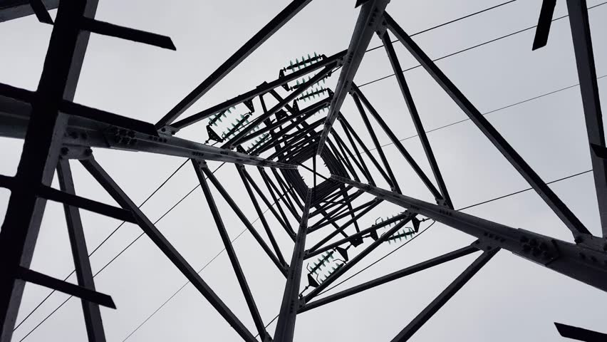 The tower of the high-voltage electric line is spinning. Bottom view. | Shutterstock HD Video #1010178524
