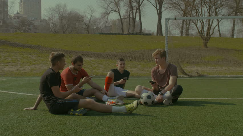 Positive football team networking with smart phones and chatting while resting on soccer pitch after game. Footballers talking and browsing social networks on cellphones while sitting on soccer field. | Shutterstock HD Video #1010180864