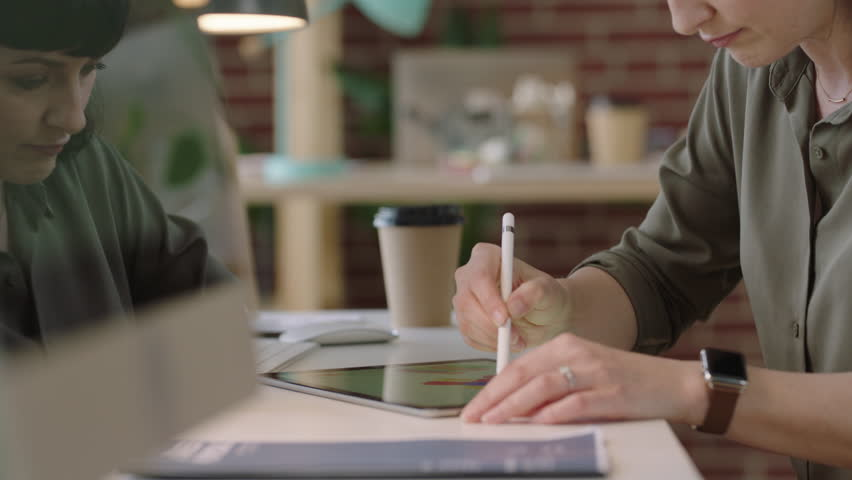 Young business woman graphic designer using tablet pc drawing on touch screen device brainstorming creative designs for corporate project | Shutterstock HD Video #1010188784