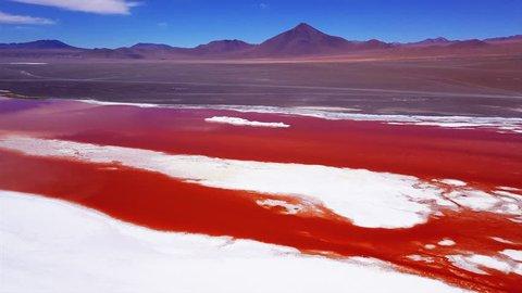 Laguna Colorada with vivid orange water and salt islets aerial shot. Altiplano, Bolivia