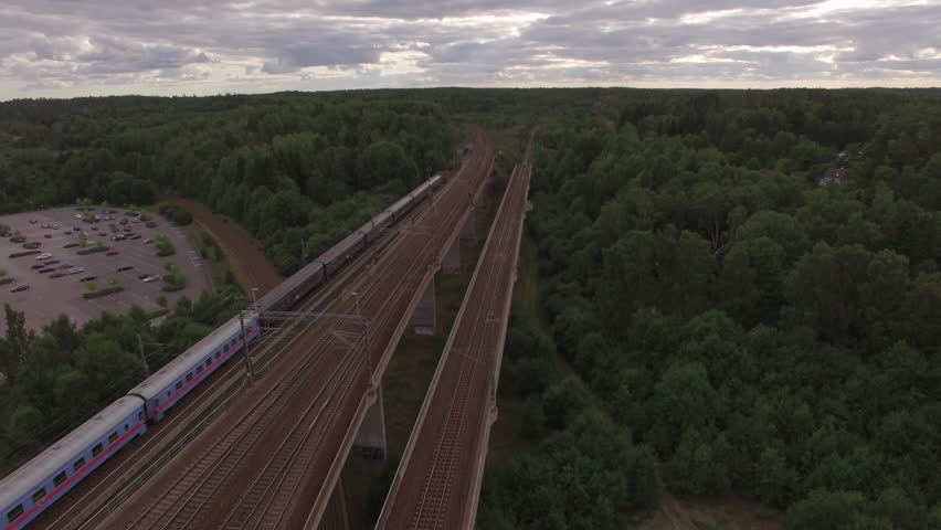 Aerial view of commuter train passing by over railway bridge in Sweden. Drone shot of railroad travel transportation | Shutterstock HD Video #1010216414
