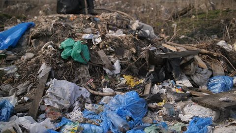 Mature homeless man in dirty clothes standing on the hill of garbage at trash dump landfill site in city. Male holding trash bin bags and old shoes. Environmental problems and pollution concept.