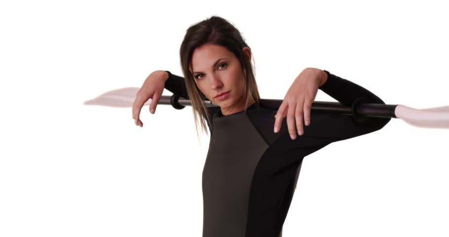 Young woman in wetsuit holding kayak paddle over shoulders on white background. Sporty female athlete in her 20s with wetsuit and oar on solid white copy space. 4k