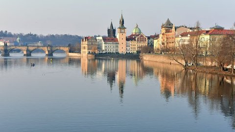 Timelapse of vltava river and charles bridge with reflections at sunset, czech republic