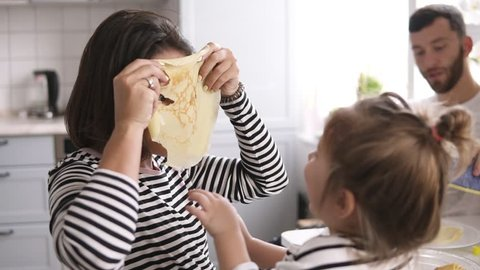 Funny mother is playing with her little daughter making comical mask with pancake on her face. Family breakfast