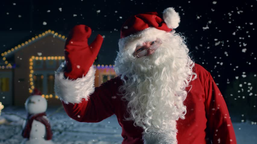Authentic Santa Claus Carrying Red Bag over the Shoulder, Walks out of the Idyllic House Decorated with Lights and Garlands. Santa Bringing Gifts and Presents. 4K UHD.