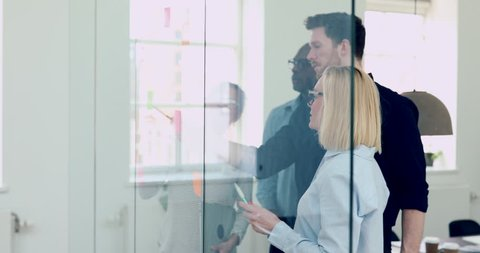 Diverse group of young businesspeople high fiving together in a modern office while brainstorming with sticky notes on a glass wall