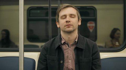 man sleeping in a underground Metro subway train. Tired worker student sleep after work, hard day, illness, fatigue, tiredness,