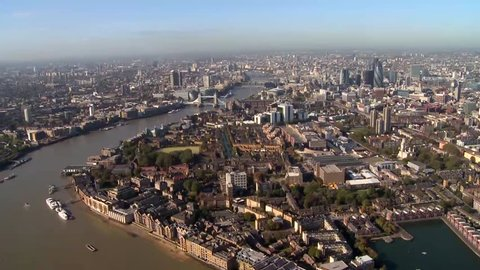 A wide travelling aerial shot of London skyline and the city. The camera follows a bend in the River Thames and we get a birds eye view of all the surrounding areas of London. HD shot from helicopter.