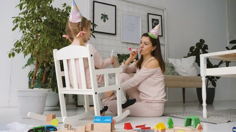 Beautiful young woman play with little cutey daughter sitting in rocking chair and blows horns. Celebration of birthday.
