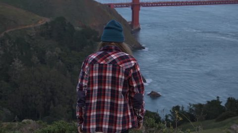 man walking down the hill with golden gate bridge view