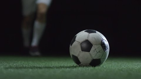 Closeup of soccer ball shoot by professional player on stadium field with artificial turf