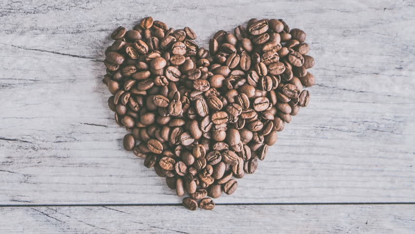 Coffee Beans swirling arond in heart shape on table Cinemagraph