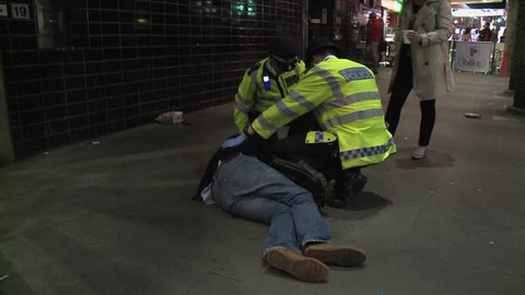 London, United Kingdom (UK) - 03 28 2012: Metropolitan police officers attend to a collapsed drunken man