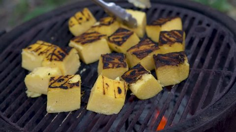Wide shot of polenta on a hot grill with grill marks.