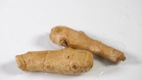 Slow motion ginger root vegetable, two whole ginger herb with water splashing on a white macro background
