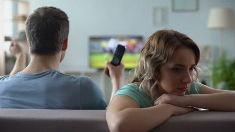 Offended girl sitting by boyfriend watching football match tv, relations crisis