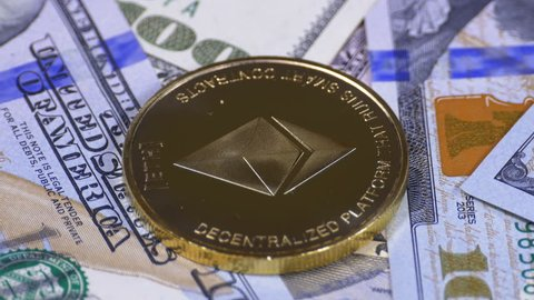 Gold Ethereum Coin, ETH and Bills of Dollars are Rotating. Crypto Currency Close-up. Dollar banknotes of various denominations on which lies the cryptocurrency.