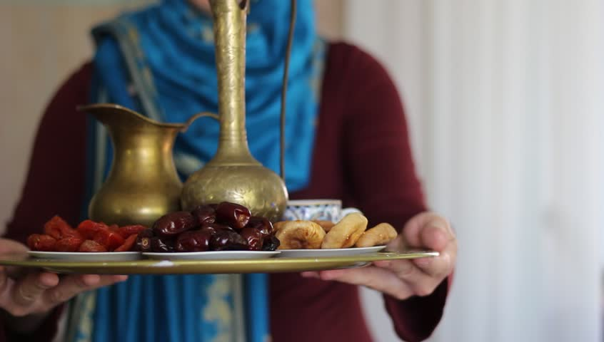Muslim woman wearing hijab. Arabic food and drink. A tray filled with bowl of sweet dates and black tea