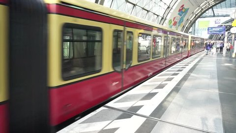 Berlin Hauptbahnhof, Germany, April 14 2018: S-Bahn train departing from Deutsche Bahn DB Main Railway Station platform, red wagons with commuters gaining speed, Berlin Central Station indoor view