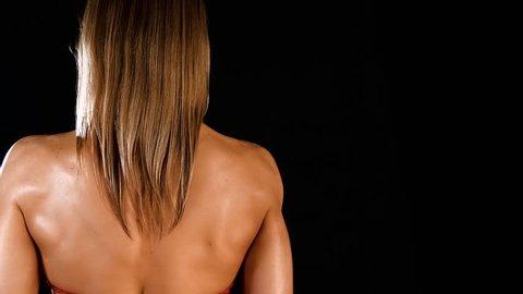 Slim Female Bodybuilder Posing In Red Bikini on a black background with copy space 4K Footage