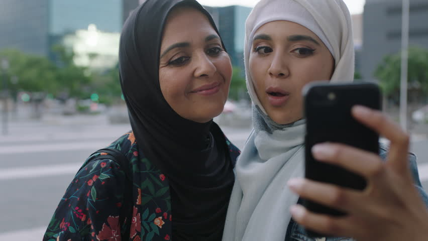 Portrait of young muslim women posing daughter kisses mother on cheek taking selfie photo using smartphone camera technology in urban city background real people series | Shutterstock HD Video #1010441204
