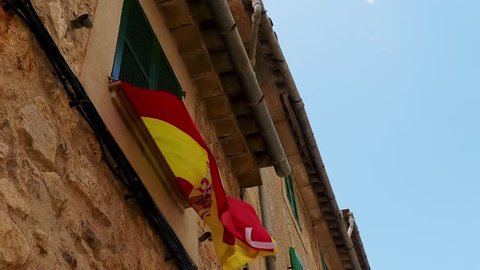 Flag of Spain (Bandera de Espana, la Rojigualda) on background of old city house.