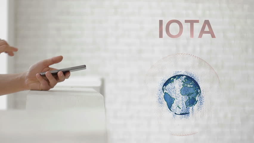 Hands launch the Earth's hologram and IOTA text. Man with future technology phone is showing a 3d projection on a modern white background